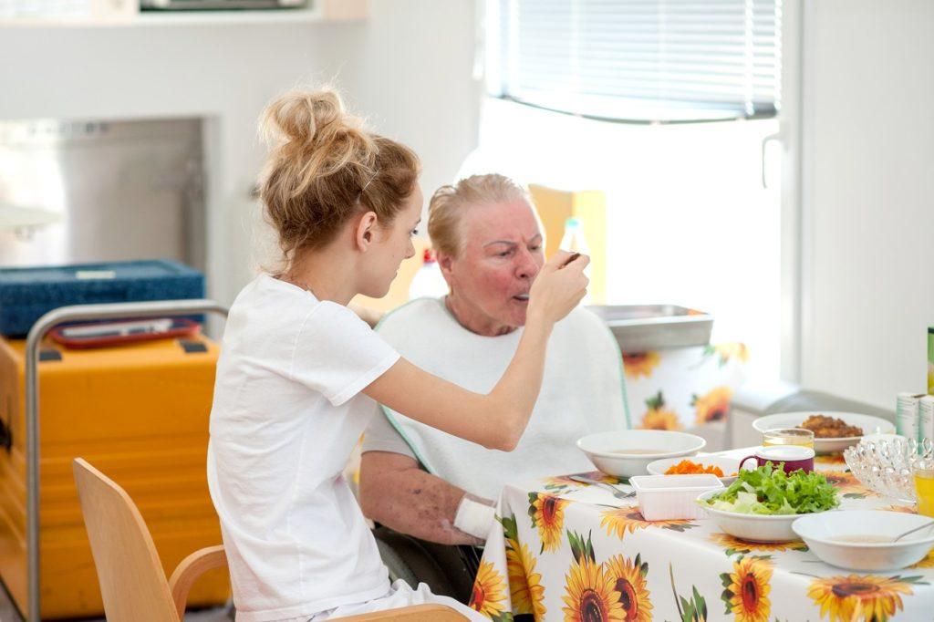 Nurse In The Nursing Home Helping Senior Woman Eating